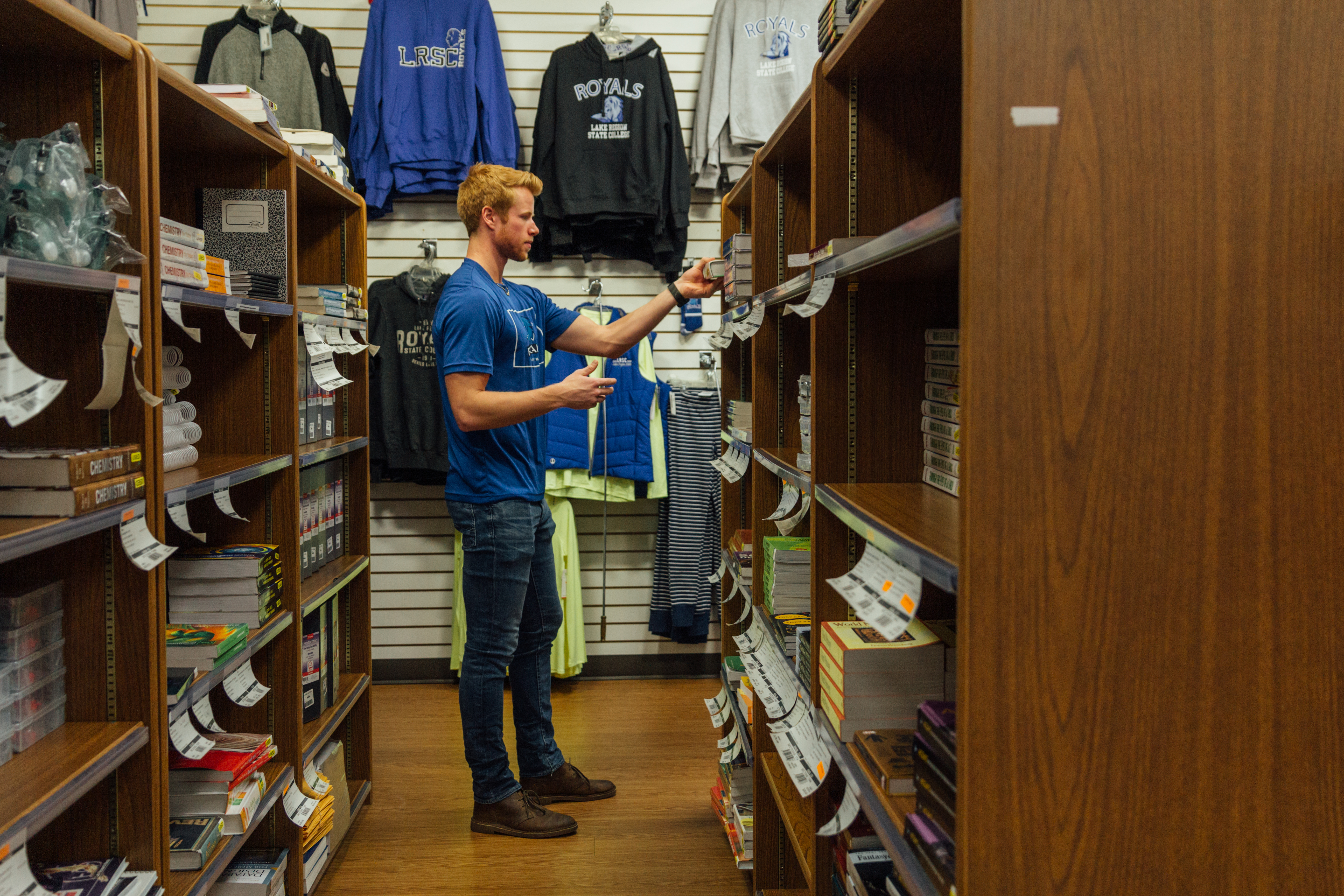Male student standing near textbooks in Bookstore